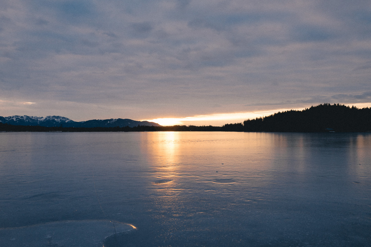 The sun goes down behind mountains in the distance. In the front is a frozen over lake.